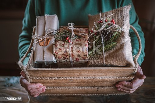 Cropped hands of unrecognizable woman puts Christmas present in wooden crate, wrapped Christmas gifts from organic recycling materials.