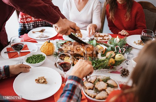 Unrecognizable people cutting and takes Christmas meal.