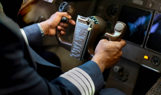 Cropped Hands of African Pilot flying a commercial airplane stock photo