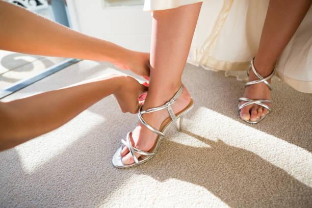 händen der kosmetikerin sandalen braut anziehen beschnitten - hochzeitskleid in schwarz stock-fotos und bilder