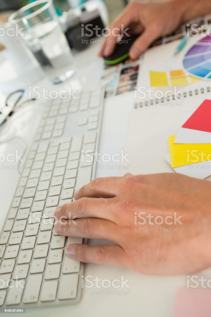 Cropped hands of businessman using computer at desk in office stock photo