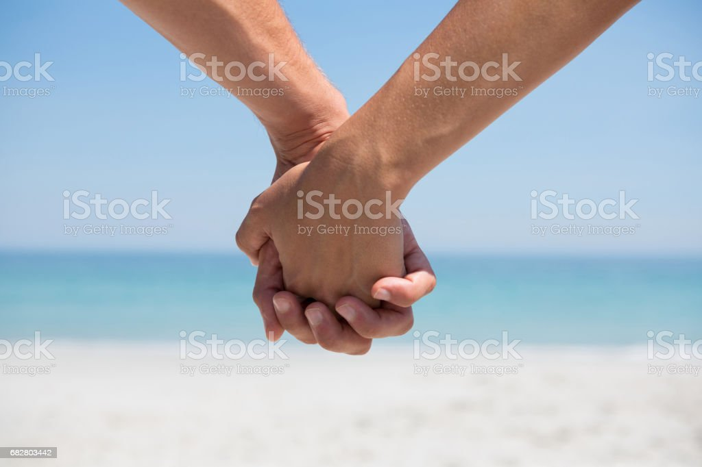 Cropped hands of couple holding hands at beach