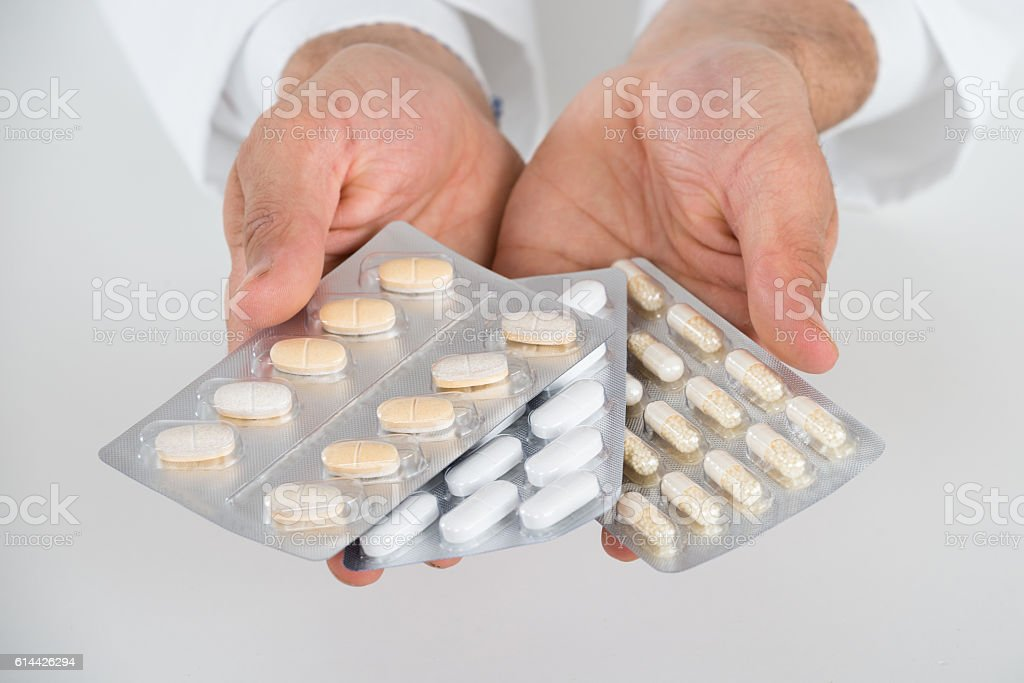 Cropped Hands Of Doctor Holding Blister Packs stock photo