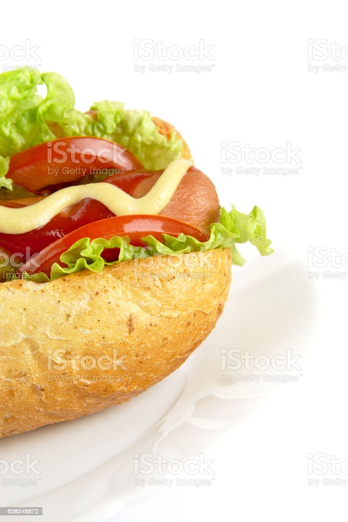 Cropped hot dog with ingredients on plate on white background stock photo