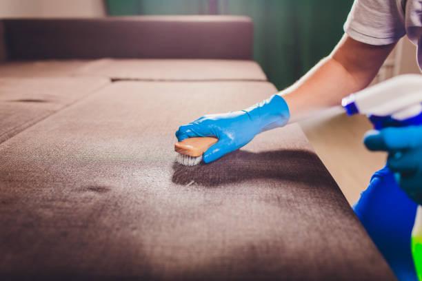 Zugeschnittenes Bild. Reinigungskonzept. Männliche Hand in hell blau schützende Handschuhe Reinigung Sofacouch im Zimmer. – Foto