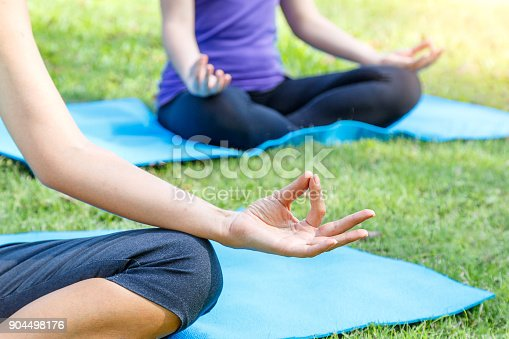 istock Cropped image group of young woman meditating in a yoga on grass in the park, yoga and healthy lifestyle concept 904498176