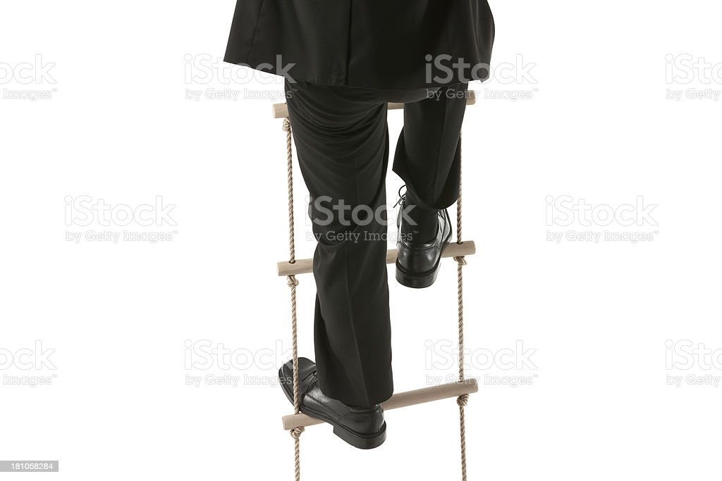 Cropped image of a businessman climbing rope ladder royalty-free stock photo