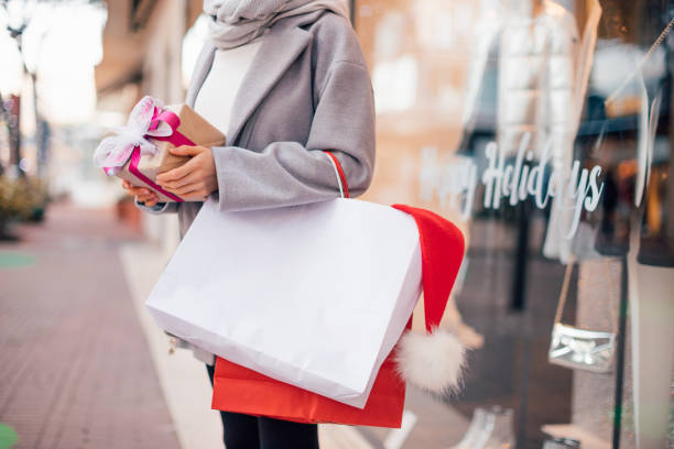 Cropped image of a girl holding Christmas presents and shopping bags, template, mock up white bag, xmas shopping concept