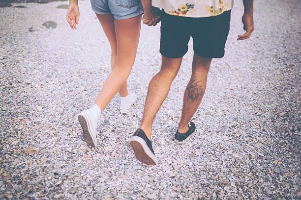 cropped bild einer hipster-paar beine zu fuß - ehepaar tattoos stock-fotos und bilder