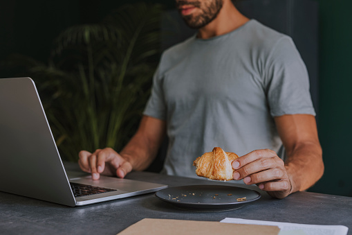Cropped image of a Man in a T-Shirt Having a Croissant for Breakfast While Working on a Laptop Computer at Home