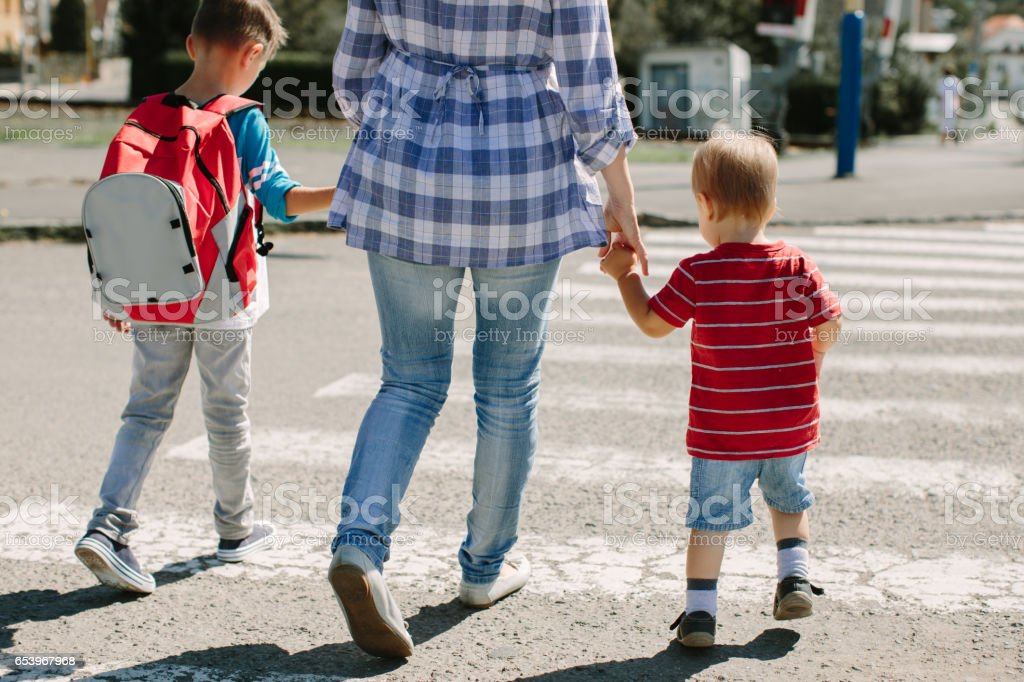 Cropped image of a mother crossing a road with her children stock photo