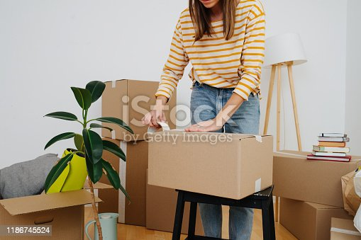 Middle age woman in casual clothes standing next to pile of boxes, packing, she's moving out from an old apartment. Sealing cardboard boxes with adhesive scotch tape. Close up, cropped, no head.