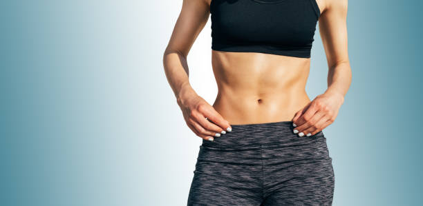 Cropped image of a young sporty woman with a muscular belly Cropped image of a young sporty woman with a muscular belly against a blue background abdominal muscle stock pictures, royalty-free photos & images