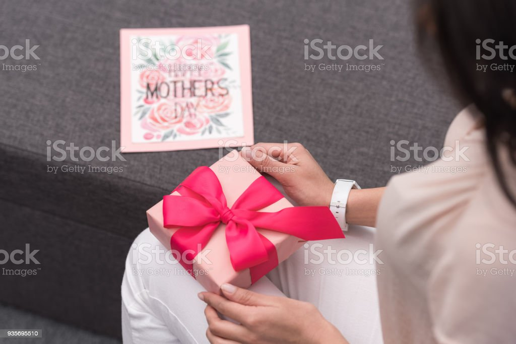 cropped image of african american mother opening present on mothers day stock photo