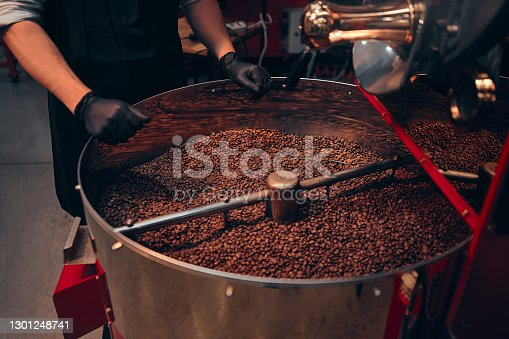 Cropped image of an african man's hands busy feeling the coffee beans after they have just been roasted to perform a quality control before the beans are packaged and shipped globally.
