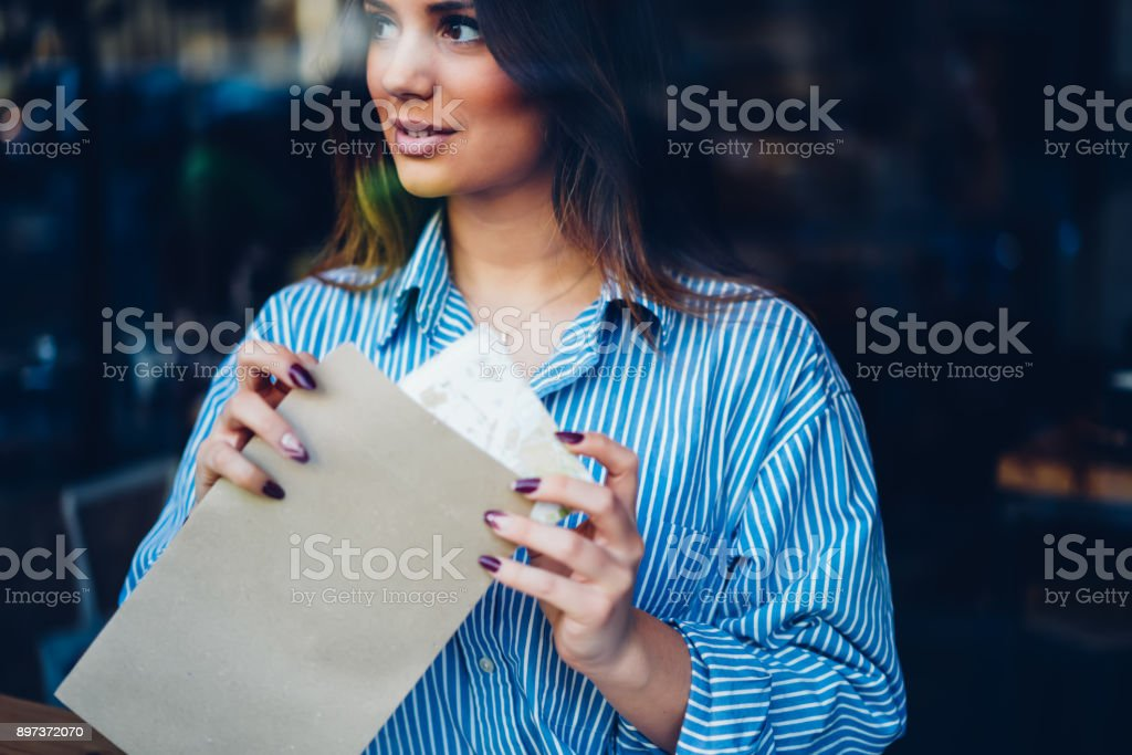 Cropped image of attractive young woman dressed in casual outfit packing envelope with mock up area for advertising text.Charming brunette hipster girl with letter in hand looking away sitting indoors stock photo