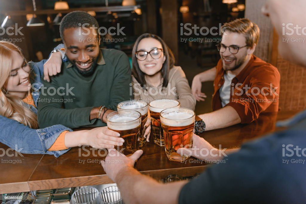 cropped image of barman giving beer to multiculture company of friends - Royalty-free Adult Stock Photo