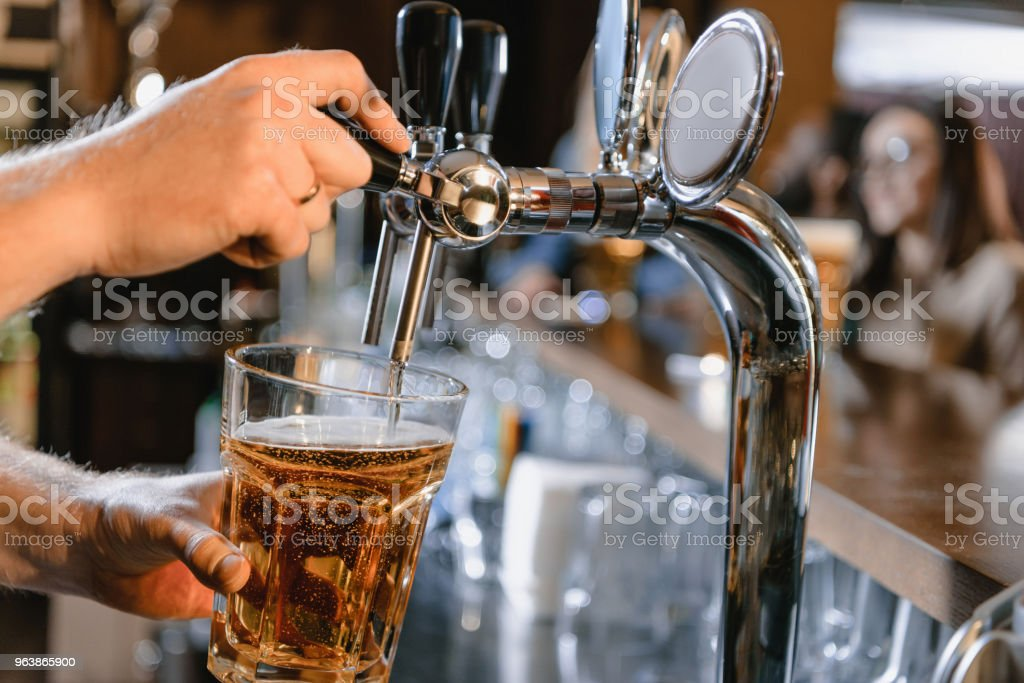 cropped image of barman pouring beer in glass at bar - Royalty-free Adult Stock Photo
