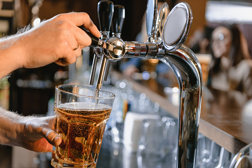 Cropped Image Of Barman Pouring Beer In Glass At Bar Stock Photo - Download Image Now
