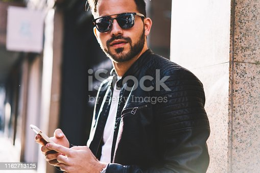 Cropped image of beaded male in sunglasses looking at camera while sending text messages via smartphone standing on city street,hipster guy chatting in social networks using modern telephone outdoors