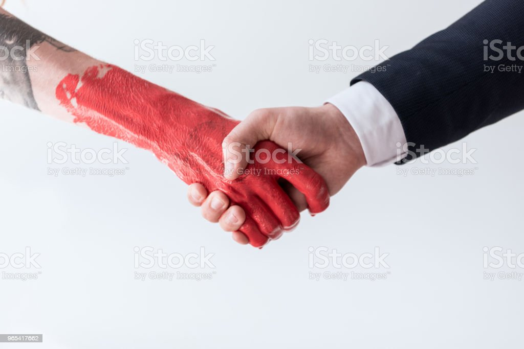 cropped image of businessman and tattooed man in red paint shaking hands isolated on white royalty-free stock photo
