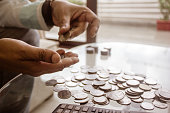 istock Cropped Image Of Businessman counting coins Using Calculator at Desk In Office. Businessperson Hand Counting Coins. 1169124785
