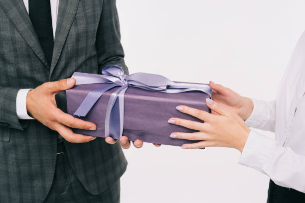 cropped image of businesswoman presenting gift to coworker isolated on white cropped image of businesswoman presenting gift to coworker isolated on white gifting stock pictures, royalty-free photos & images