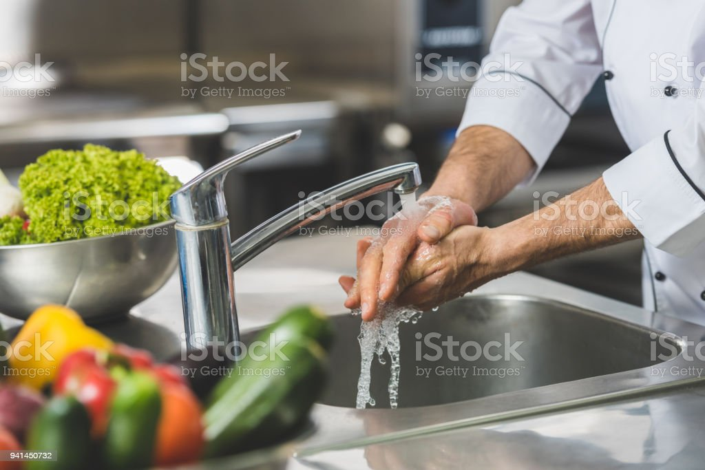 cropped image of chef washing hands at restaurant kitchen stock photo