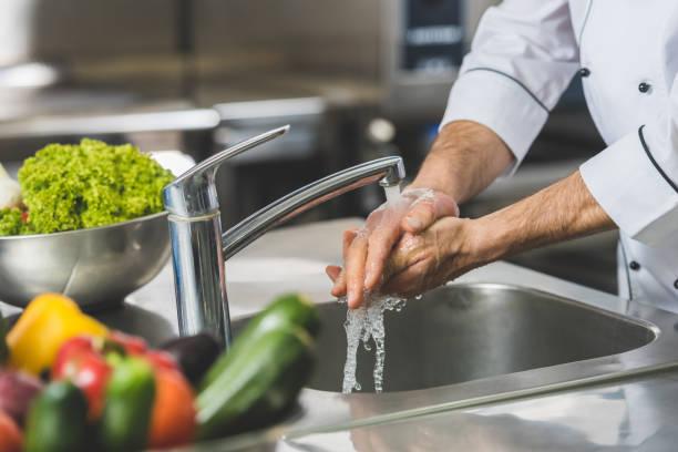 bijgesneden afbeelding van chef-kok wassen van de handen bij restaurant keuken - rijp voedselbereiding stockfoto's en -beelden
