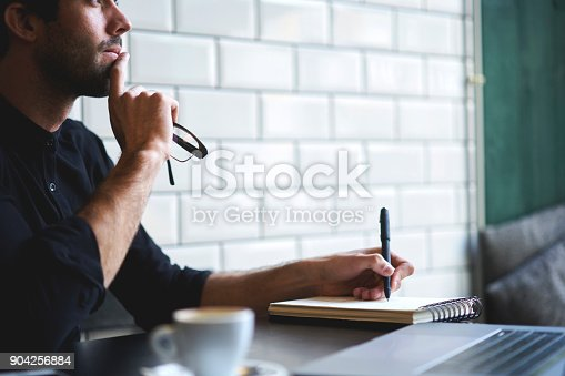 istock Cropped image of concentrated thoughtful male freelancer thinking on personal startup project and writing ideas to notebook sitting in coffee shop.Copy space area for your advertising text message 904256884