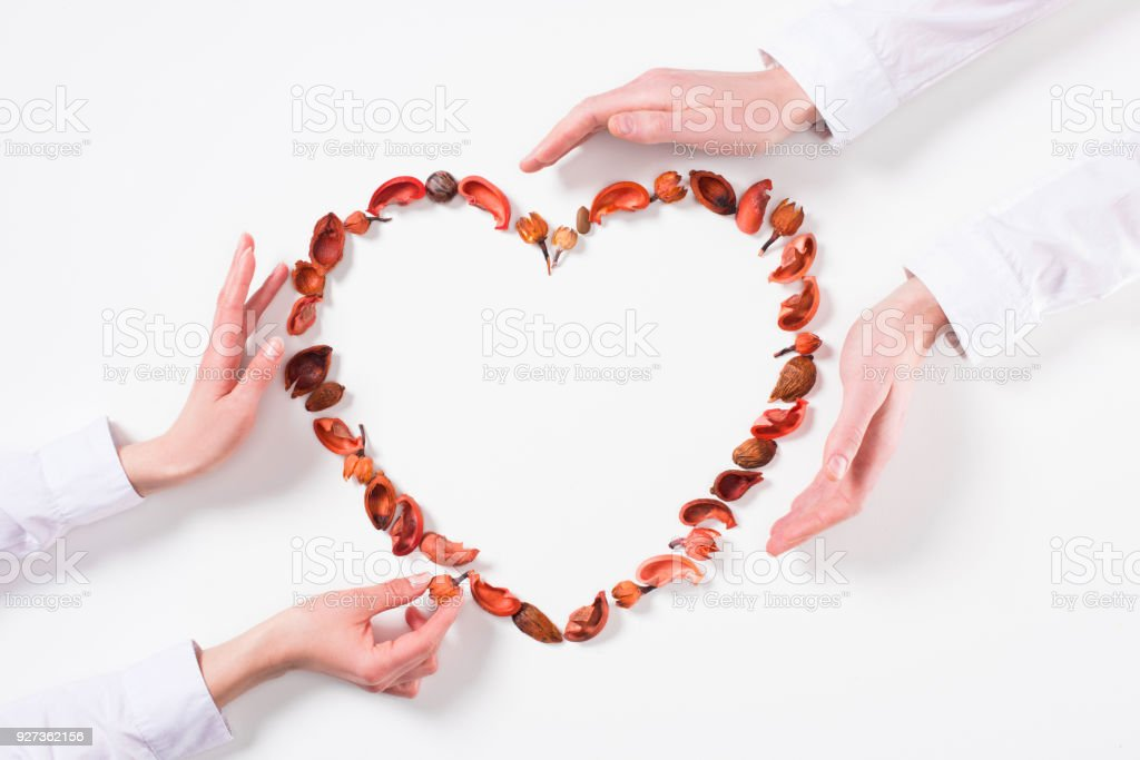 cropped image of couple making heart from dried fruits on valentines day on white - Royalty-free Adult Stock Photo