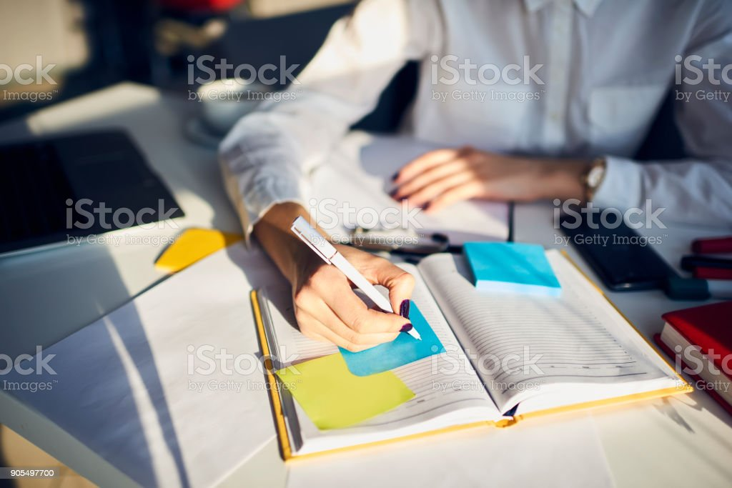 Cropped image of creative female secretary creating planning for executive noting important meeting and events organizing work of busy boss while sitting at working place in coworking office stock photo