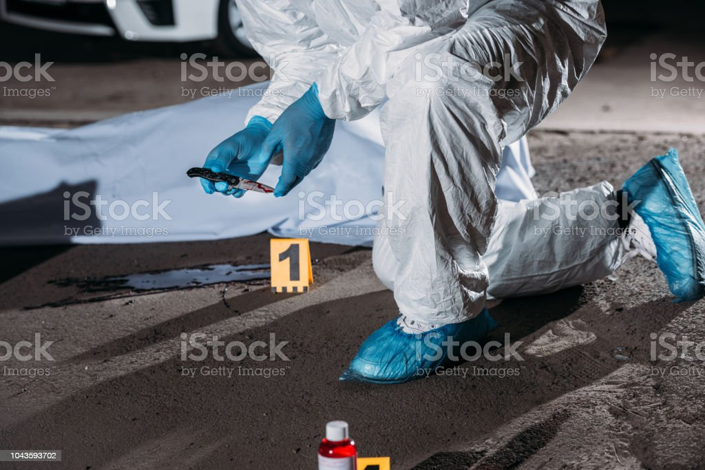 cropped image of criminologist in latex gloves and protective suit holding knife above blood on ground near corpse in body bag at crime scene stock photo