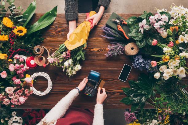 cropped image du client de payer par carte de crédit pour le bouquet - fleuriste photos et images de collection