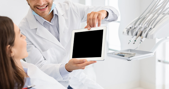 Cropped image of dentist showing blank digital tablet screen