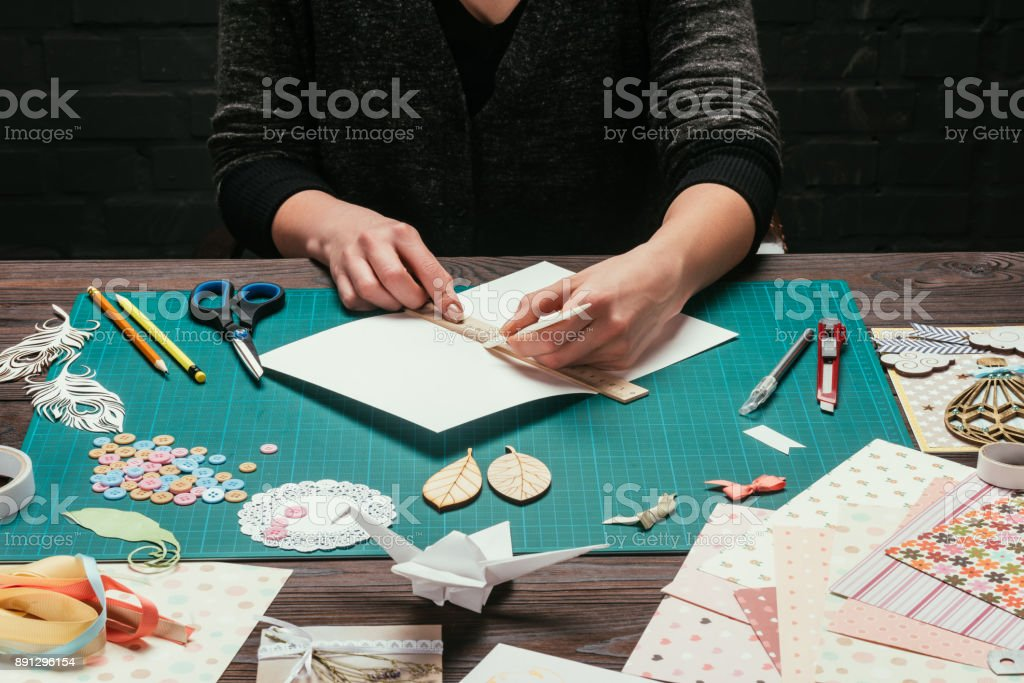 cropped image of designer cutting paper for scrapbooking greeting postcards stock photo