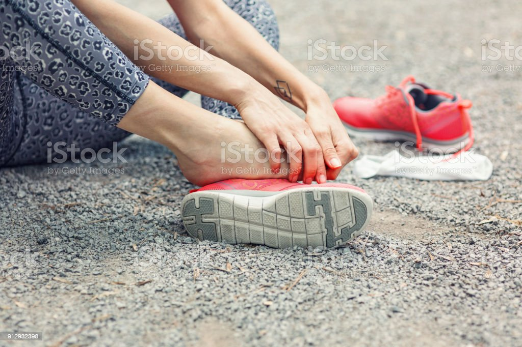 Cropped image of female hands massaging her injured foot stock photo