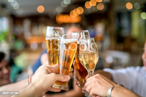 Cropped image of people toasting drinking glasses. Friends are celebrating and enjoying at bar. They are spending leisure time in restaurant.