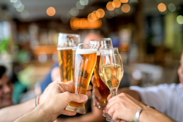cropped image of friends toasting drinks in celebration. - happy hour stock photos and pictures