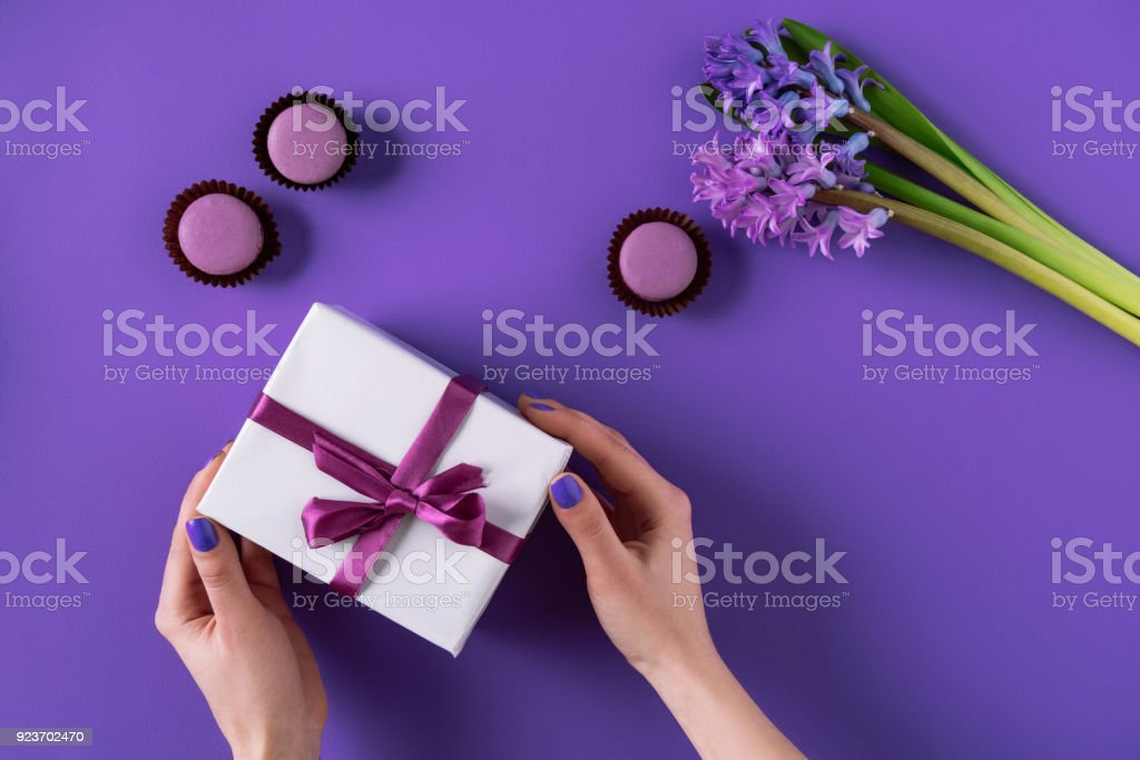 cropped image of girl holding present box on purple stock photo