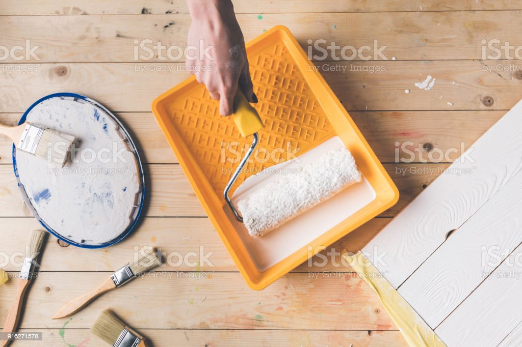 cropped image of girl putting paint roll brush in white paint