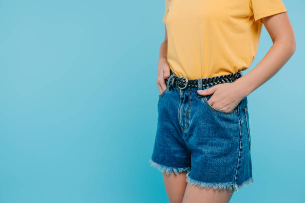cropped image of girl standing with hands in pockets isolated on blue cropped image of girl standing with hands in pockets isolated on blue shorts stock pictures, royalty-free photos & images