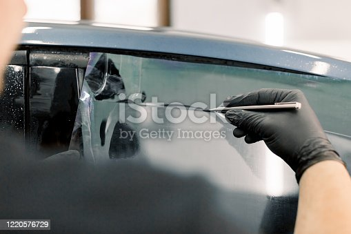 Cropped image of hands of worker in garage tinting a car window with tinted foil or film, holding special blade or knife to cut the film. Car detailing workshop, tinting windows.