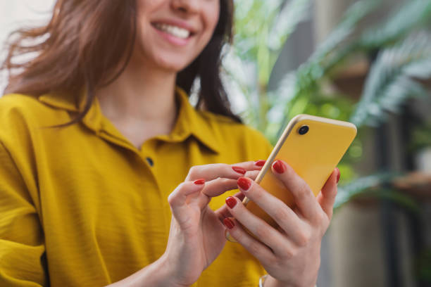 imagen recortada de la chica feliz usando el dispositivo del teléfono inteligente mientras se relaja en casa - sin personas fotografías e imágenes de stock