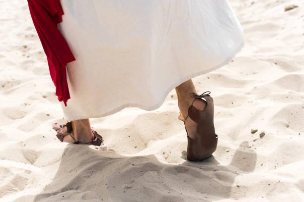 가운, 샌들, 모래 사막에서을 걷고 빨간 창틀에 예수의 이미지를 자른 - 샌들 뉴스 사진 이미지