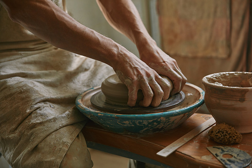 cropped image of male craftsman working on potters wheel at pottery studio