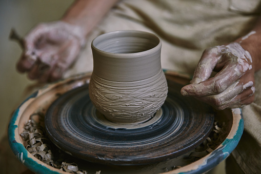 cropped image of male craftsman working on potters wheel at workshop