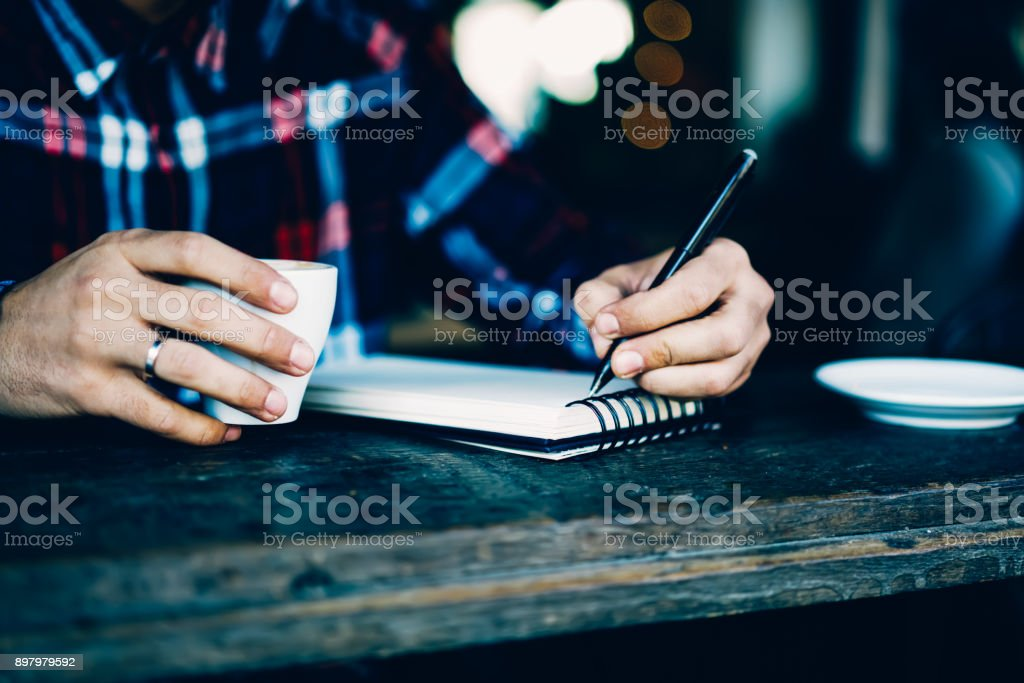 Cropped image of male\'s hands holding pen and writing down text...