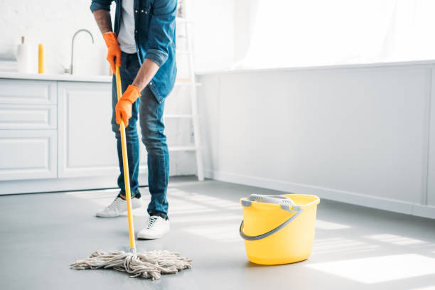 cropped image of man cleaning floor in kitchen with mop cropped image of man cleaning floor in kitchen with mop mop stock pictures, royalty-free photos & images