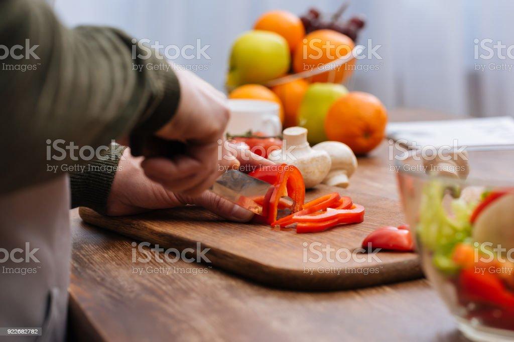 キッチンに赤ピーマンを切る男のトリミングされた画像 ストックフォト